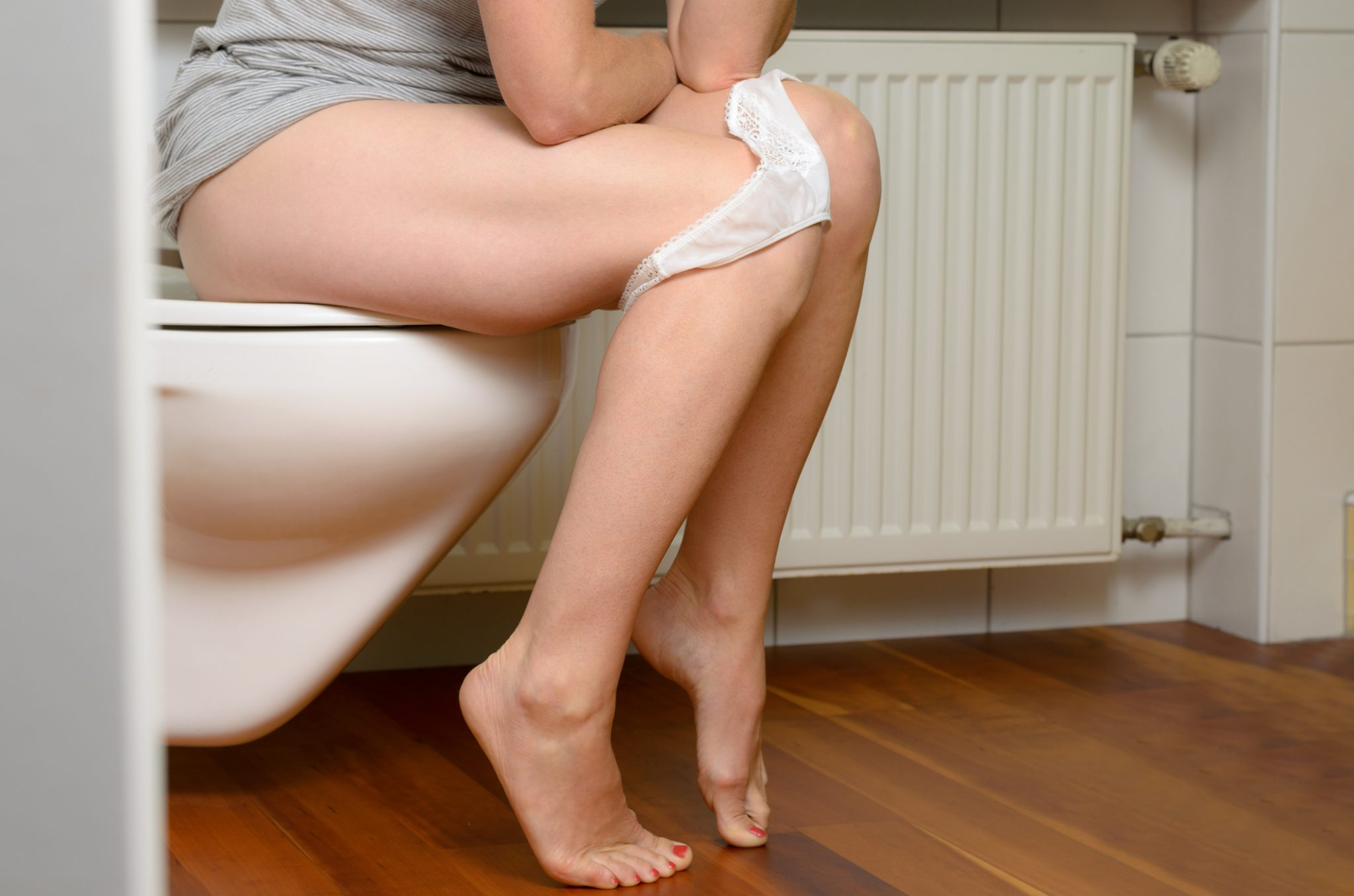 woman pelvic exercise on a toilet - kegel